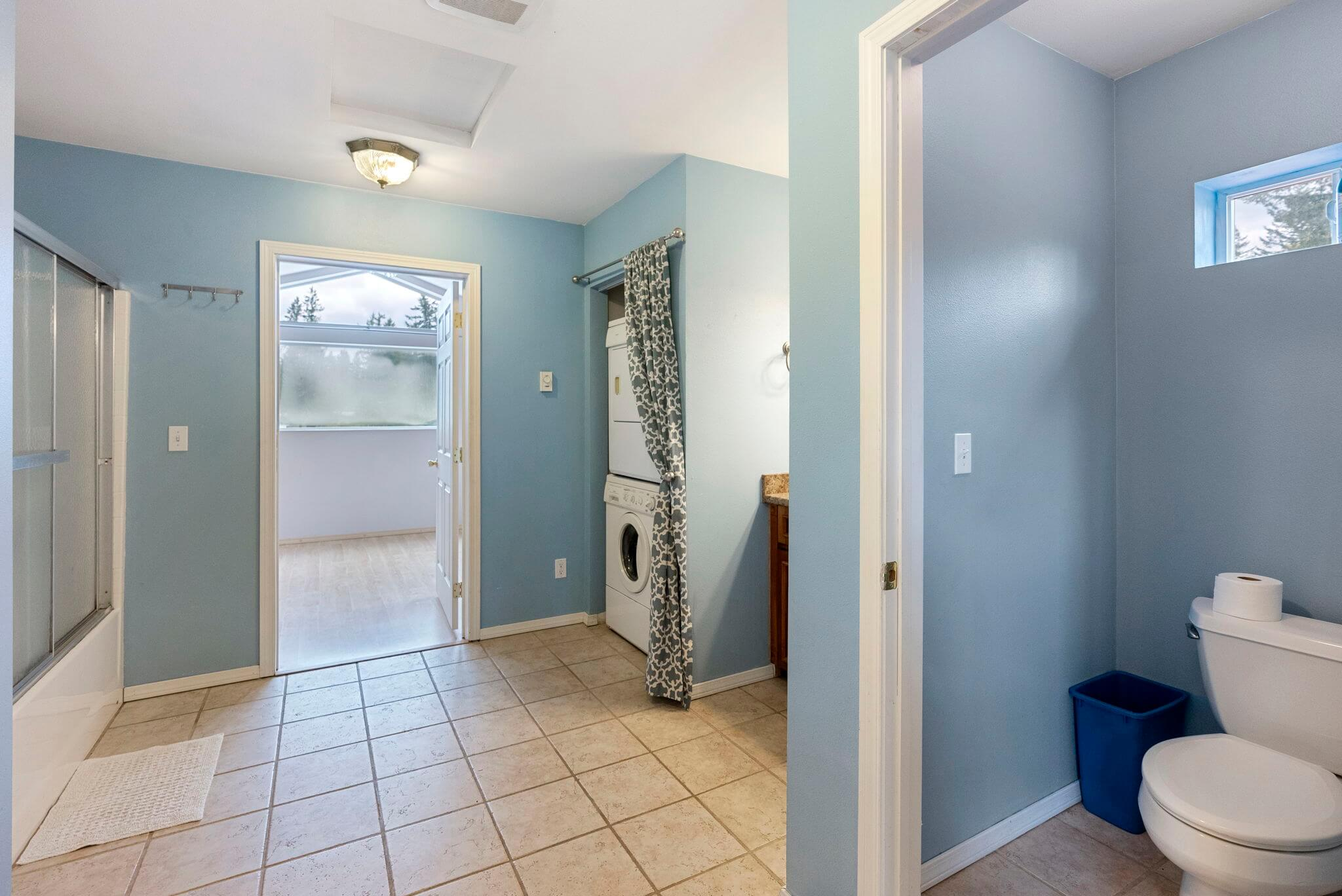 Full bathroom with stacked washer/dryer